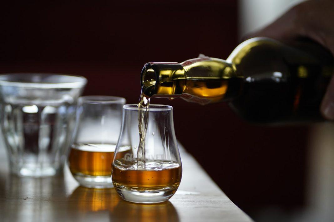 Un homme servant du Whisky dans un verre sur un comptoir de bar