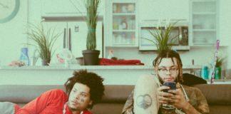Deux jeunes hommes installés dans un divan avec des smartphones en main.