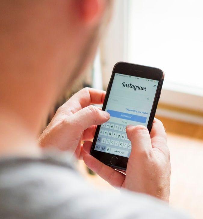 Un jeune homme manipulant son téléphone avec une page Instagram sur l'écran.