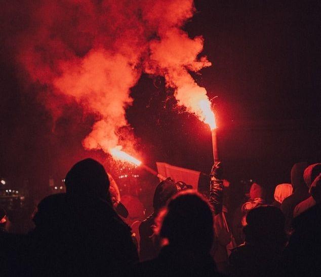 Des manifestants nocturnes avec des flambeaux levés.