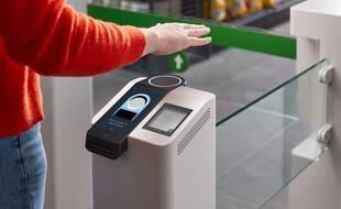Un homme posant la main au dessus d'un terminal de paiement