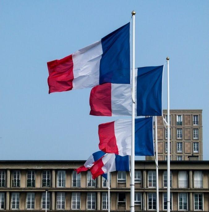 Des drapeaux de France devant un bâtiment public.